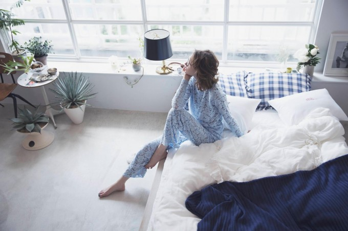 パジャマを着てベッドに座る女性