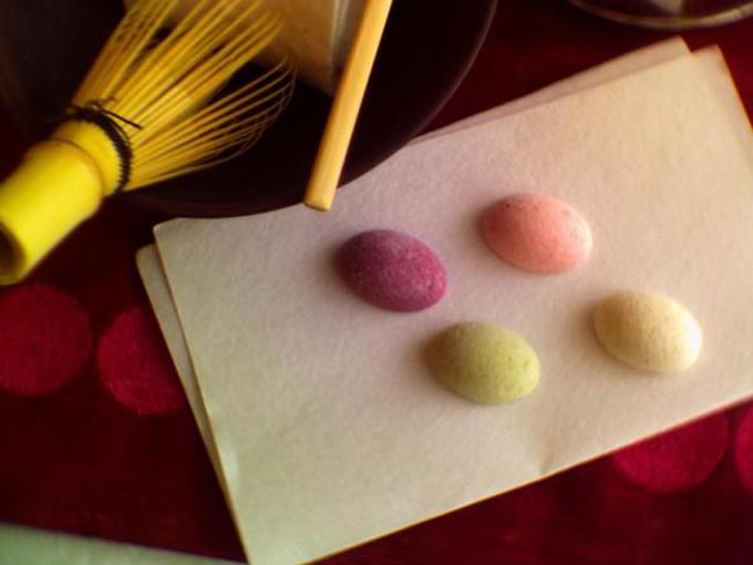 懐紙の上にのったピンクや黄緑のカラフルな和菓子と茶筅