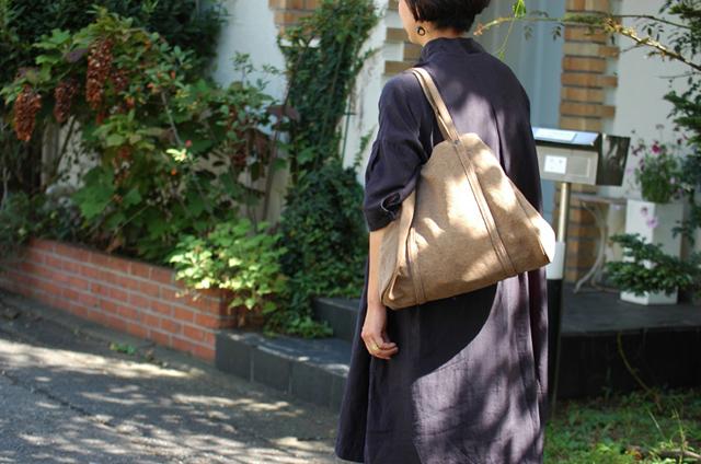 ブラックのワンピースとベージュのトートバッグ