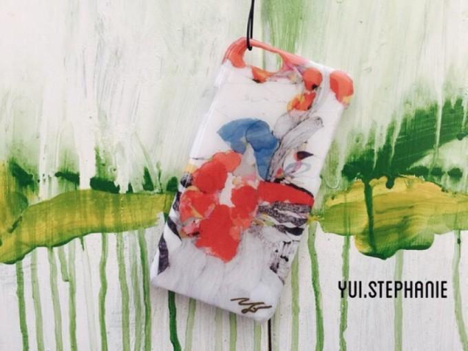 絵画作品の一部をデザインした白地に赤や青などのカラフルなスマホケース