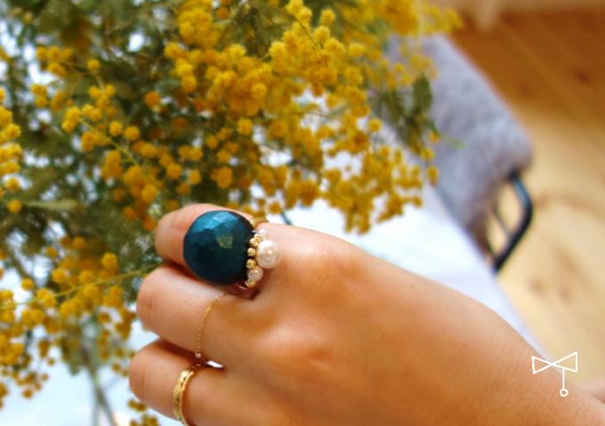 OZAKI(オザキ)のボタンアクセサリーを付けた女性の指と黄色のお花