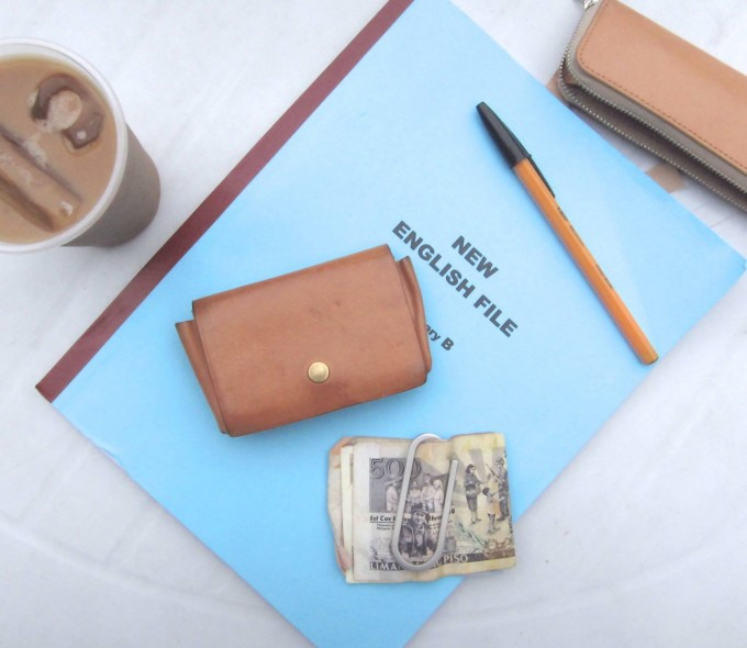 ブルーのノートの上に置かれたブラウンのレザーウォレット