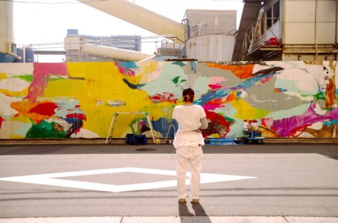 国道沿いの壁に書いたカラフルな絵と画家