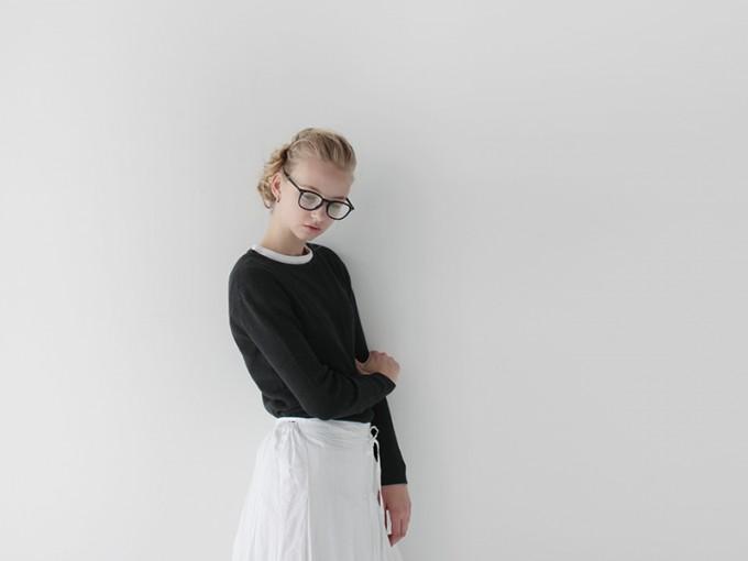 Veritecoeur(ヴェリテクール)の黒いプルオーバートップスと白いスカートを履いたモデル