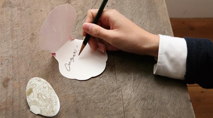 「paperable(ペパラブル)」の貝がら型のシェルメモカードにメッセージを書いている写真