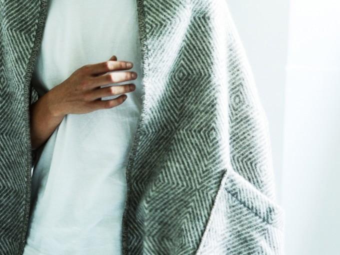 グレーのウールポケットショールを羽織る女性