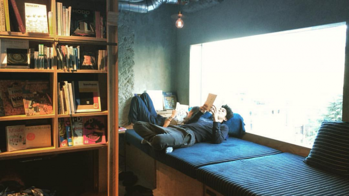 BOOK AND BED TOKYO(ブックアンドベッドトーキョー)のロビーにある青いソファで本を読む男性