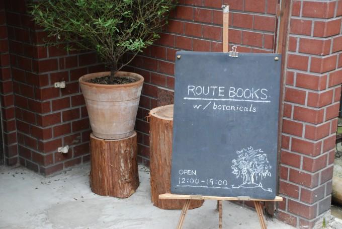 赤茶色のレンガの壁の前に出ている黒板にROUTE BOOKSと書かれた看板の写真