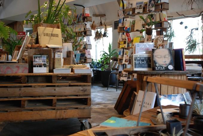 DIYの木の机に本や画集やグリーンが並んでいるお店の写真