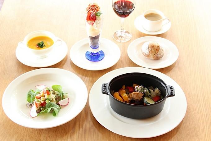 前菜やストウブに入った料理やスープ、コーヒー、ワインがテーブルに並んだ写真