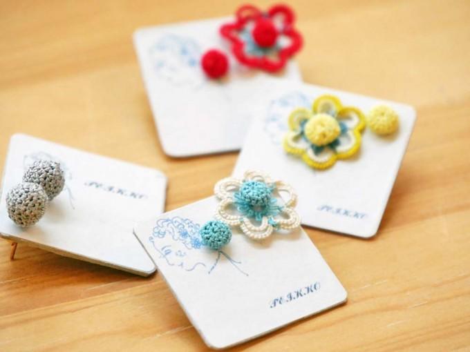 galerie doux dimancheで販売しているレース糸やラメ糸をかぎ針で水色、白、黄色、赤色の花モチーフに仕上げたpeikkoのピアスの写真
