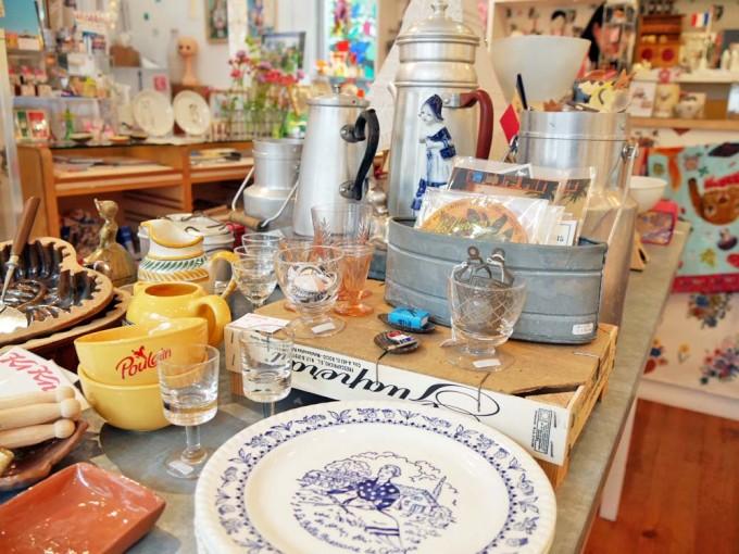 白に青文字のプレートや黄色い陶器ボウルや小さなワイングラスなどのフランス輸入雑貨が並ぶギャラリー・ドゥー・ディマンシュの店内の写真