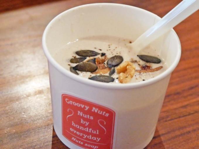アーモンドミルクにスモークドベーコンやかぶやシメジが入ったクリーミーな白いホットスープが白いカップに入っている写真