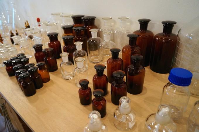 薬用、実験用の茶色や透明のフタ付き瓶が並ぶ清澄白河「リカシツ」の木の棚の写真
