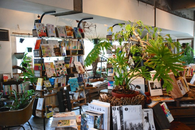 観葉植物と本が本棚に並ぶ白い壁に打ちっぱなしのブックカフェROUTE BOOKSの内観の写真