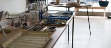 細く黒い足のテーブルに青い布やアクセサリーがディスプレイされている「組む東京」の店内