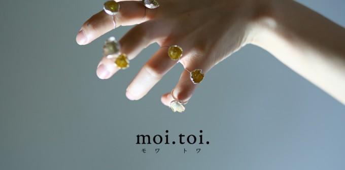 moi.toi.(モワトワ)のジュエリー数種類をつけた女性の手とロゴ