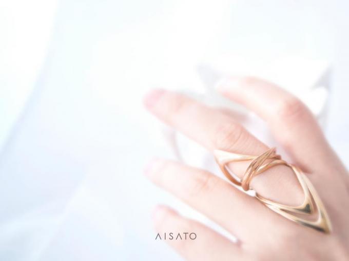 aisato(アイサトウ)の金属がループしたデザインのリングをつけた手