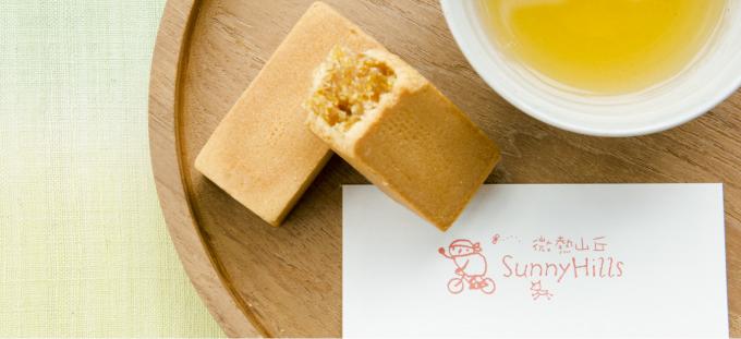 Sunny Hills(サニーヒルズ)のロゴが描かれた紙とパイナップルケーキとパイナップルジュースと