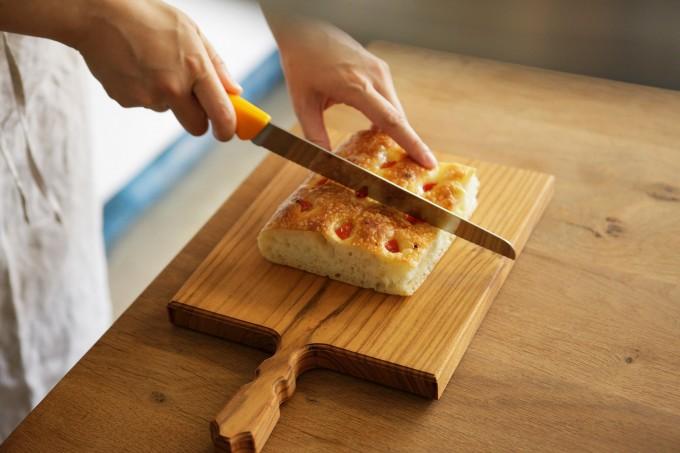 woodpecker(ウッドペッカー)の山桜のまな板の上でパンを切っている人の手