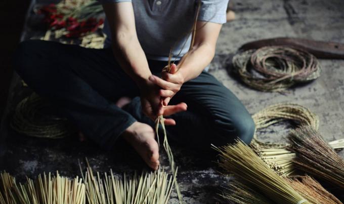 藁(わら)を編んでいる男性