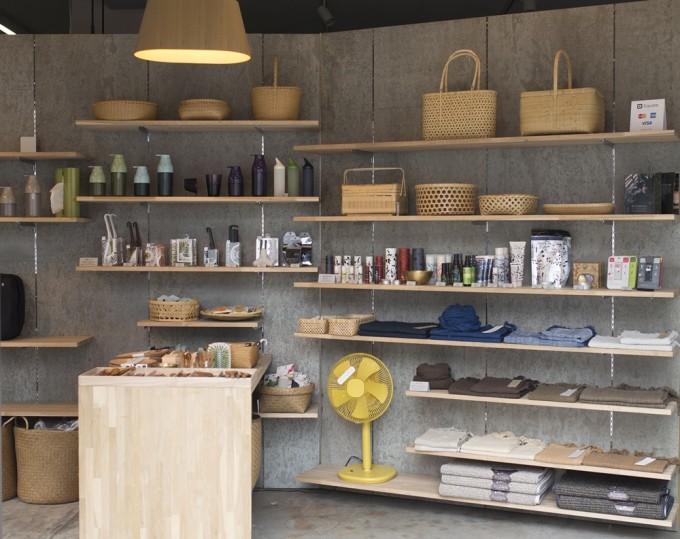グレーの壁に付いた木の棚にカゴや黄色い扇風機やディスペンサーや青い布が並ぶ写真