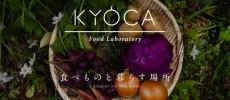かごに花や玉ねぎ、ミョウガ、じゃがいもなどがのったKYOCAのロゴイメージ