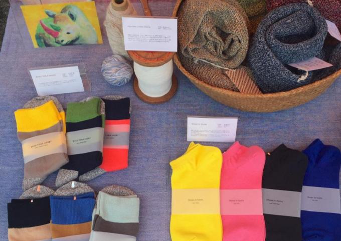 テーブルに置かれたニットデザインにしなの靴下やストール数種類