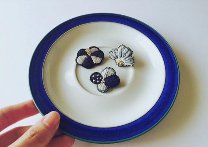 手に持った青いお皿の上に乗ったacou:(アク)のお花モチーフの刺繍ブローチ3種類