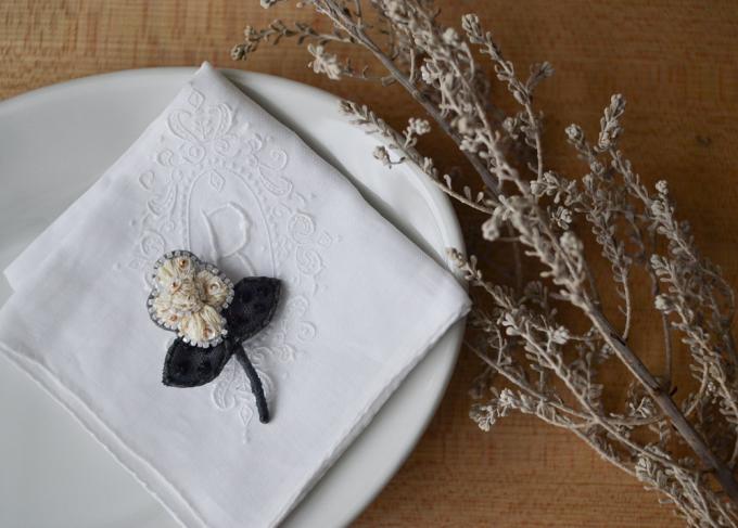 お皿の上に乗ったacou:(アク)のお花モチーフの刺繍ブローチと植物