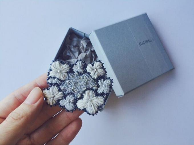 acou:(アク)のパッケージとお花モチーフの刺繍ブローチを持つ手