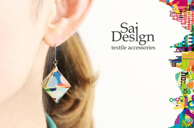 Sai Design(サイデザイン)の天然木に紙を貼り付けて作ったピアスを着けている女性とロゴ