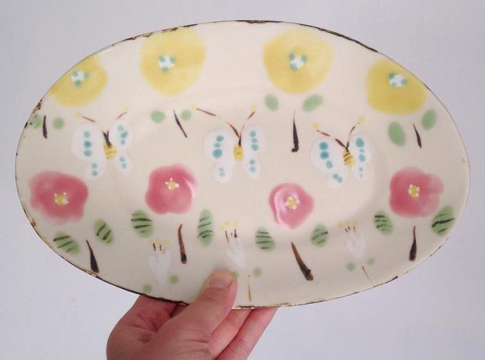 花やちょうちょが描かれた石木文(いしきふみ)さんのお皿を持つ手