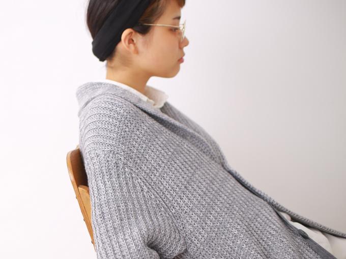 toiro(トイロ)のカーディガンを着て椅子に座る眼鏡の女性