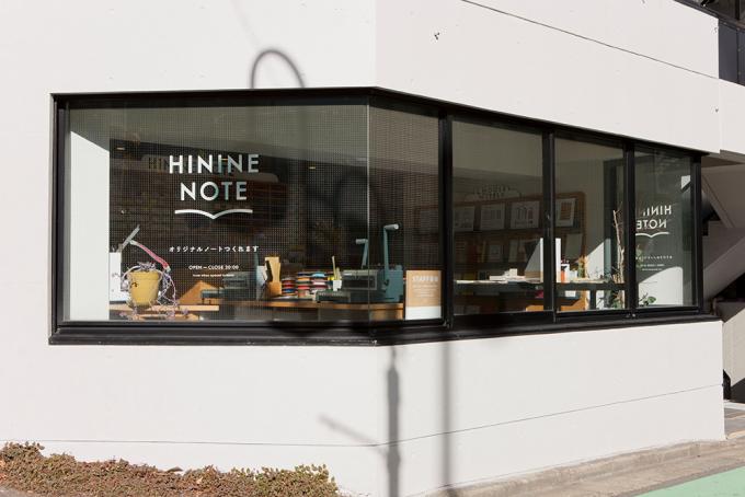 ガラス張りで白い壁のビルの「HININE NOTE」
