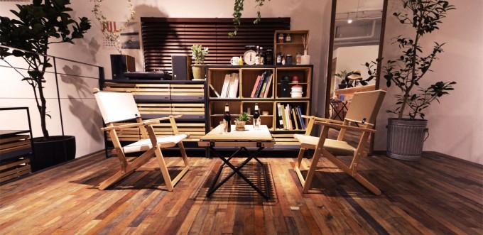 天然木フローリングに木のアウトドア椅子やシェルフが並んでいる、INOUTの店内