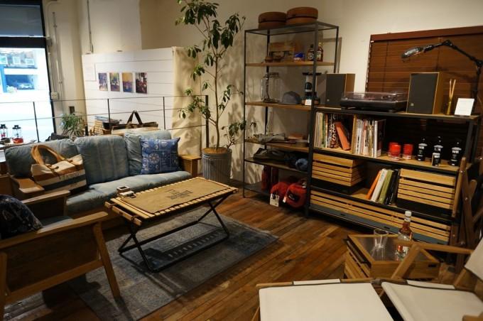 天然木フローリングに木のアウトドア椅子やシェルフが並んでいる「INOUT」の店内