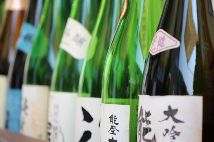 能登の日本酒の緑や茶色の一升瓶がたくさん並んだ写真