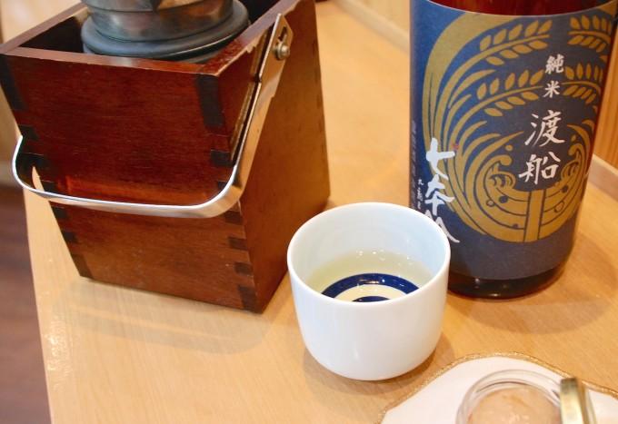 木の御燗セットと白いおちょこと日本酒の瓶がカウンターに並んだ鈴木酒販の角打ちの写真
