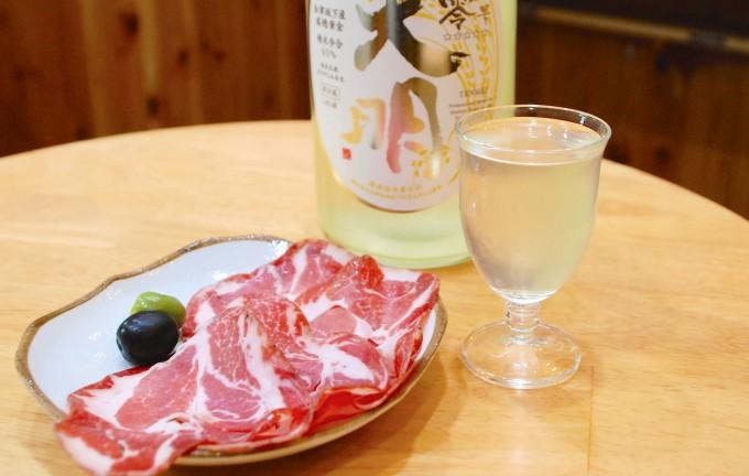 生ハムとグラスに注がれた日本酒と天明の透明な一升瓶