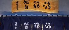 日暮里にある銭湯「斉藤湯」の入り口の木の看板と暖簾