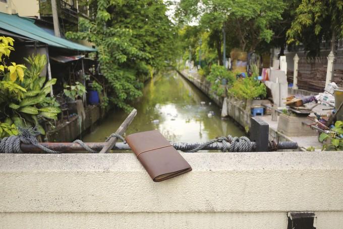 旅の途中の川沿いに置かれた茶色い革の「トラベラーズノート」