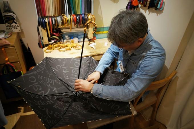 レディースとメンズの傘が並ぶ東京ノーブルの御徒町の店内で傘を職人が傘を作っているところ