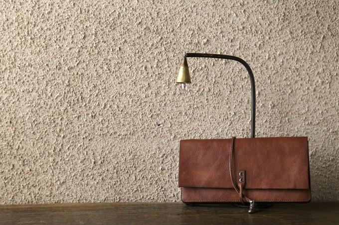 照明の下に置かれた茶色いヴィンテージレザーの長財布
