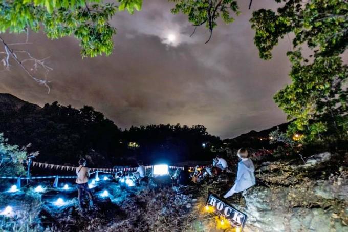夜空に月が見える『夜空と交差する森の上映会』の会場