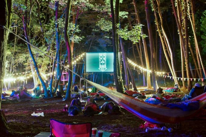 木にハンモックが結ばれた『夜空と交差する森の上映会』の会場