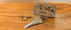 ゲストハウス雪結のロゴが入ったキャッシュトレーの上に乗った鍵
