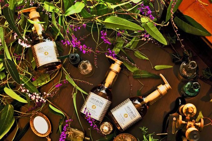 アーユルヴィストのアビヤンガ ボディウォッシュ」のボトルと紫の花