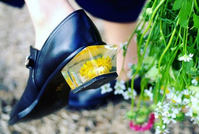 MABATAKI MIUのヒールにお花が入った靴を履いた女性の足