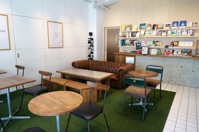 木のテーブルがあり人工芝のマットが敷かれた、白を基調としたカフェ「TRIPLE R(トリプルアール)」の店内